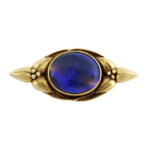 "Margaret Rogers (1868-1949) pin / brooch with floral decoration centered by an inset cabochon stone 1 3/8""w x 1/2""h"